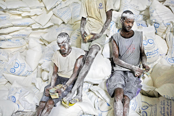 ©Pascal Maitre/National Geographic Il riposo degli scaricatori Operai contano la paga dopo aver scaricato un camion di farina in Somalia